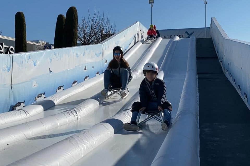 Familias disfrutando del tobogán de hielo ecológico