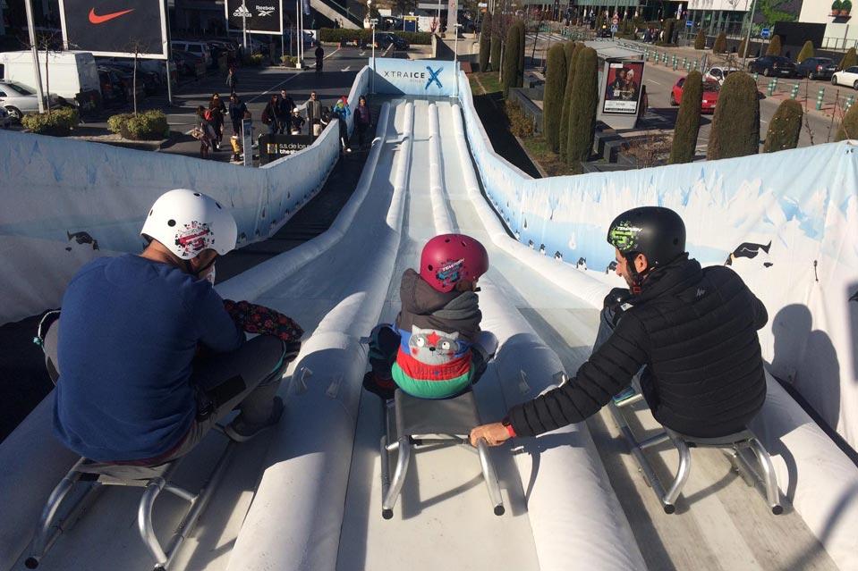 Niños y adultos a punto de tirarse por el tobogán de hielo ecológico instalado en San Sebastián de los Reyes